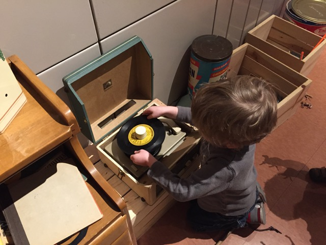 boy putting a record on a record player inside the Lustron house at Ohio History Center