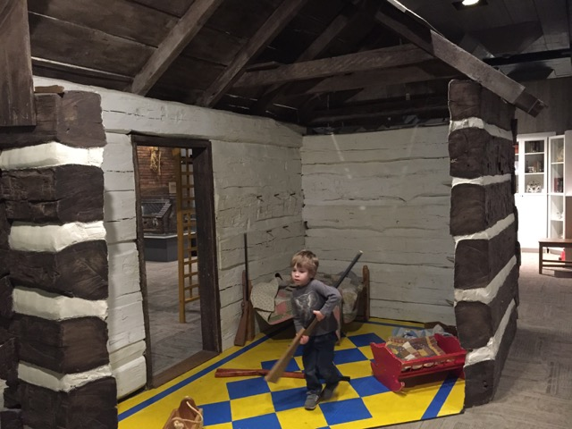 boy playing in the log cabin area at Ohio History Center