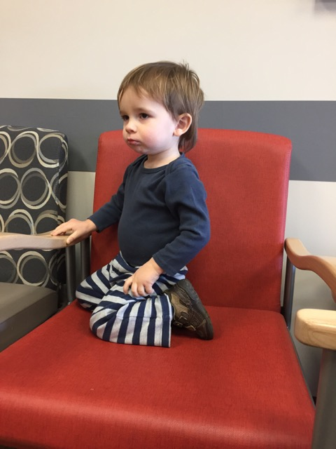Sitting at the doctor's office looking sad.