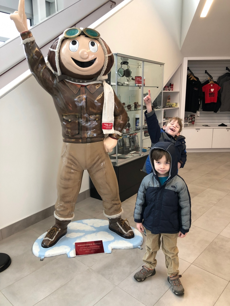 boy standing next to Brutus Buckeye at OSU Airport
