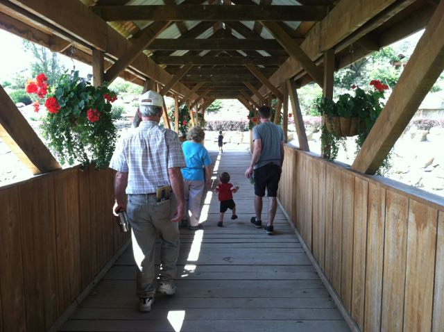 family walking across a bridge