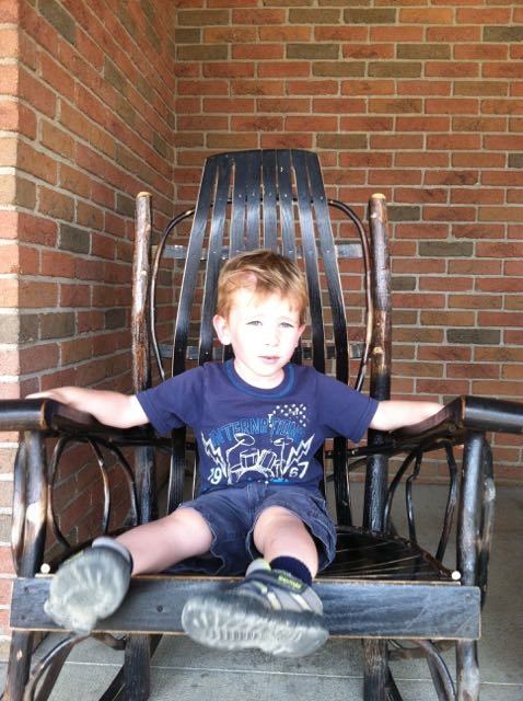 boy sitting on a rocking chair outside Der Dutchman