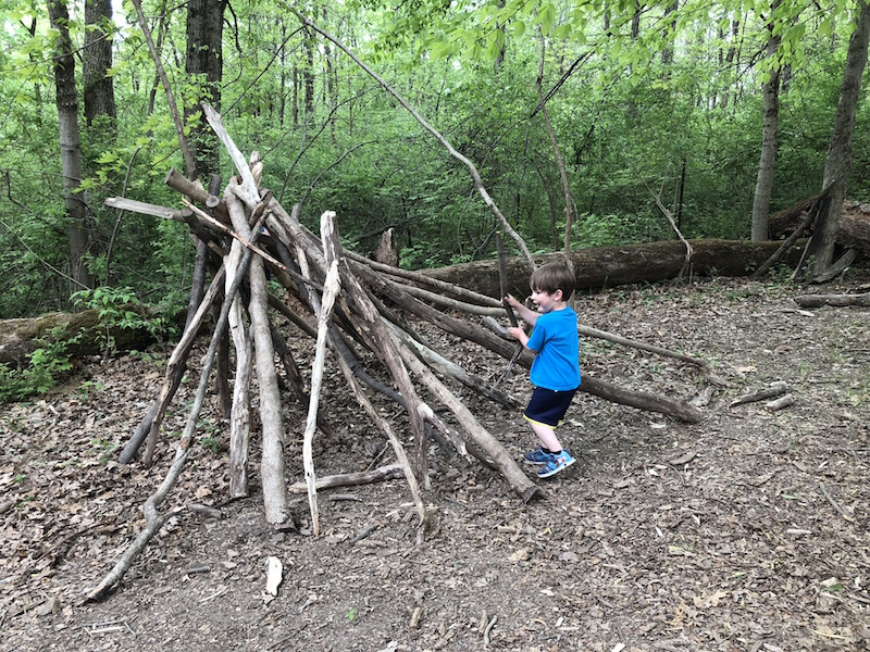 boy playing in a stick fort at the Natural Play Area