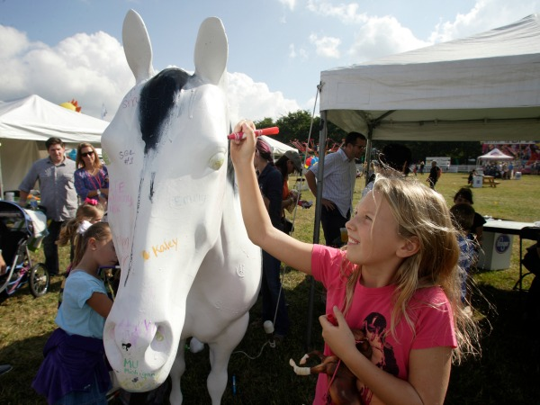 Carys Wasil, 10, of Blacklick signs the Ohio State University Equine Department's horse statue during the New Albany Classic Sunday, Sept. 21, 2014.