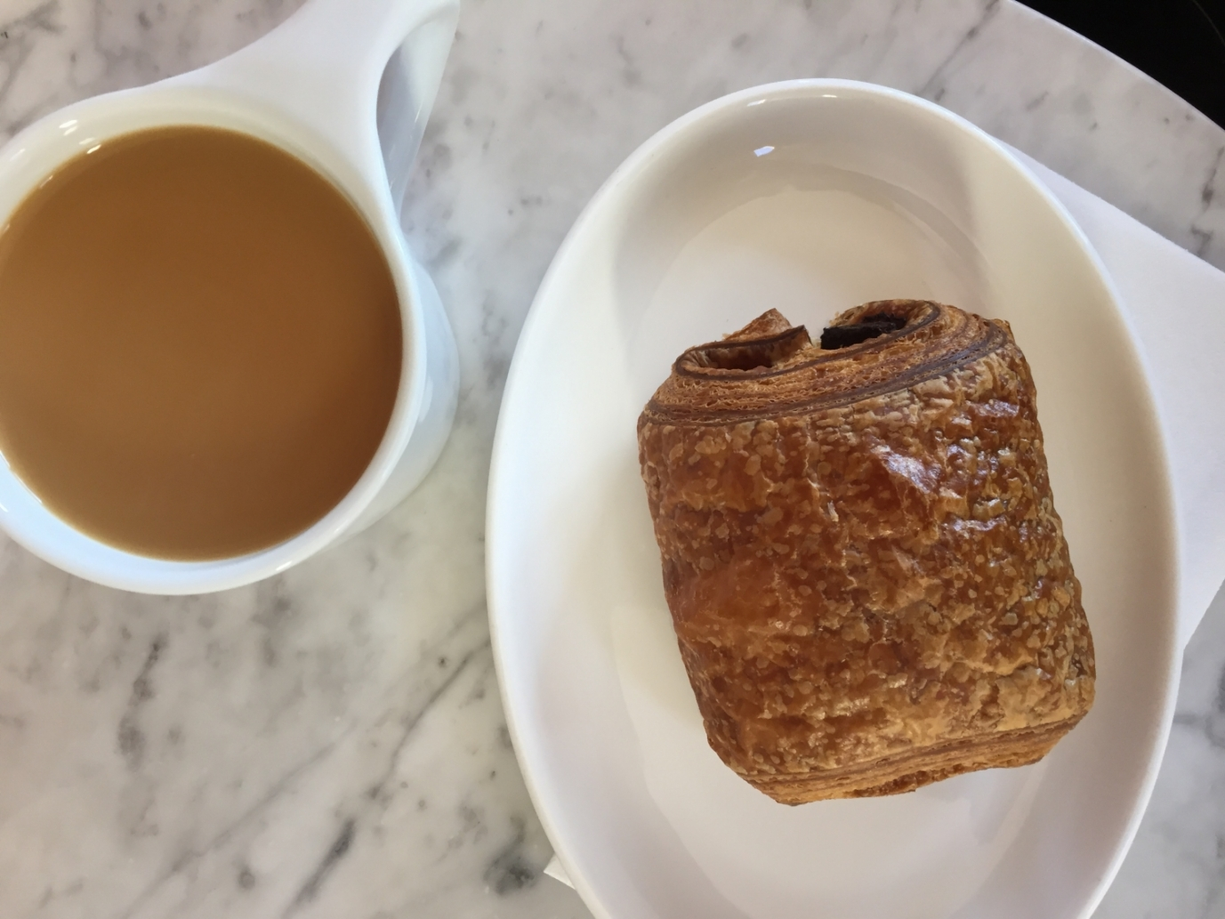 a cup of coffee and Pain Au Chocolat from Pistacia Vera, a french bakery in Columbus Ohio