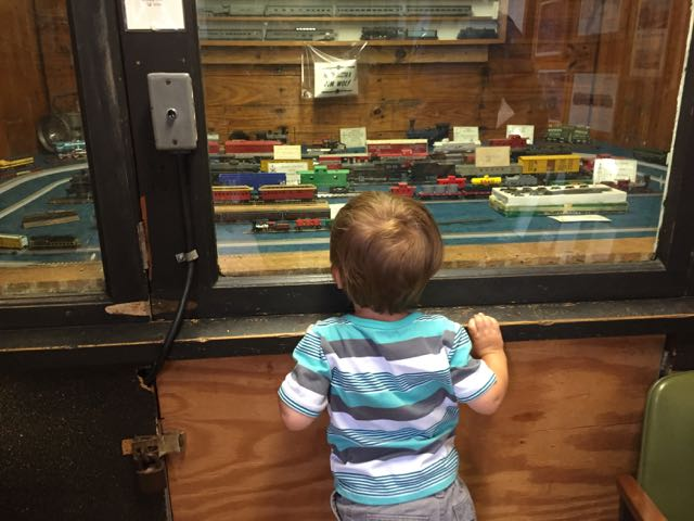 boy looking at a model train at the museum