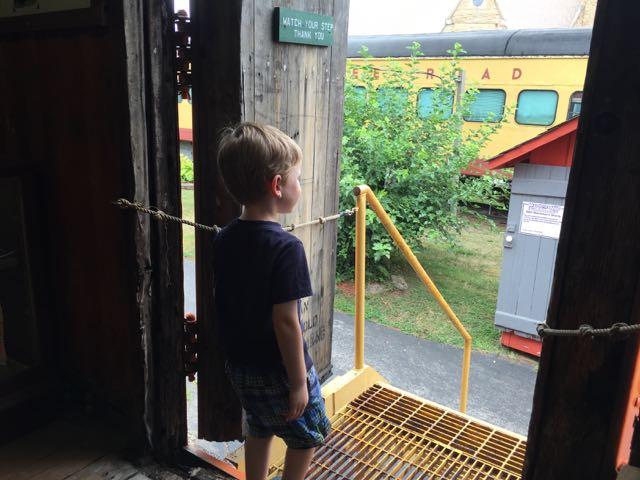 boy looking out the door of the train car