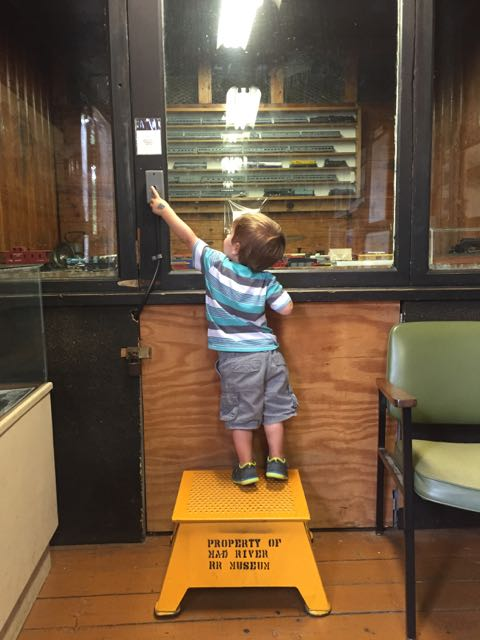 boy pressing the button to make the train go at the NKP Railroad Museum