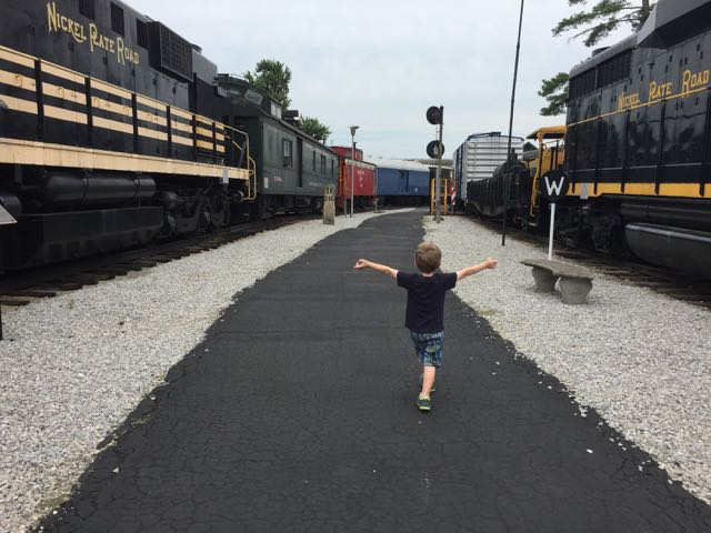 boy walking through the outdoor portion of the train museum
