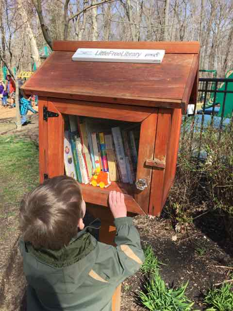 kid getting a book from a little free library in columbus, ohio