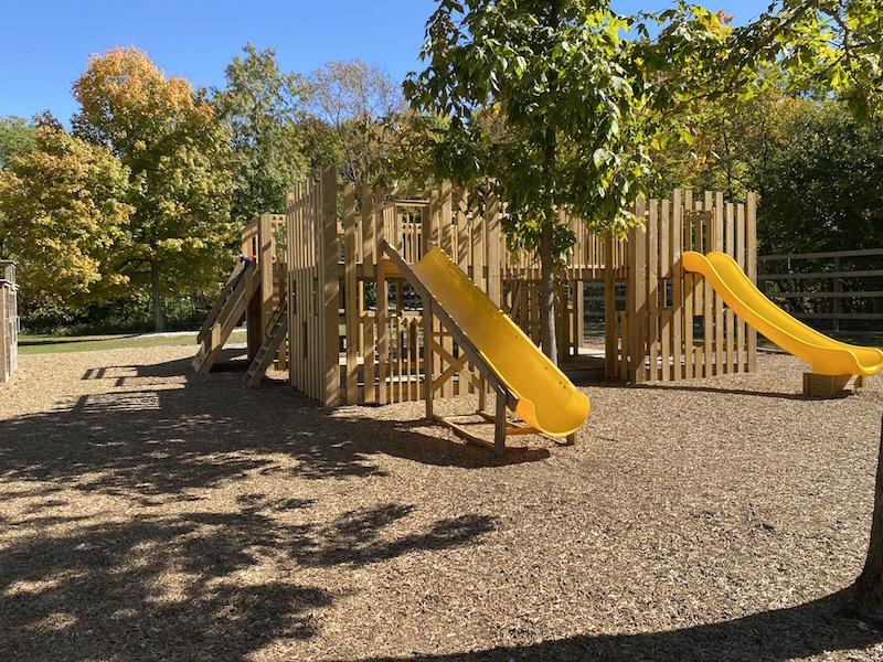 wooden playground area with yellow slides