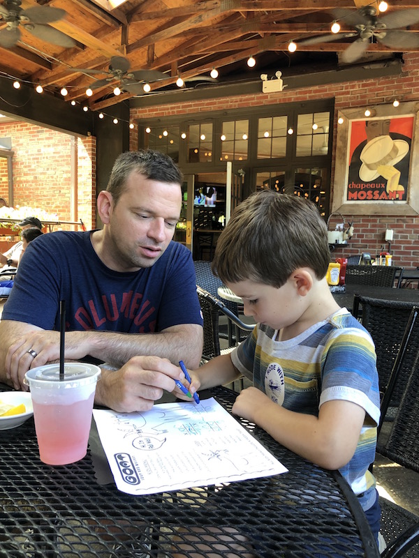 boy and father coloring on the kids menu at The Goat