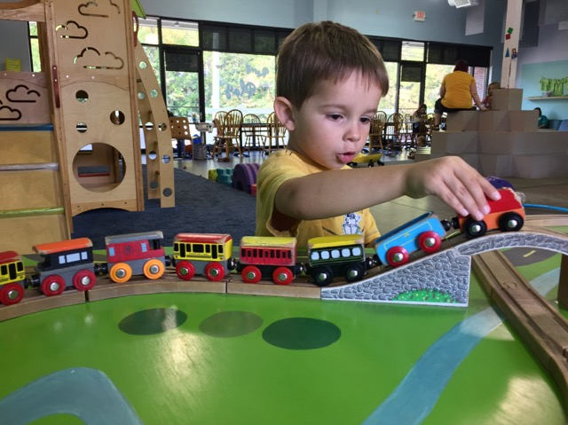 boy playing with a train at Firefly Play Cafe in Columbus, Ohio