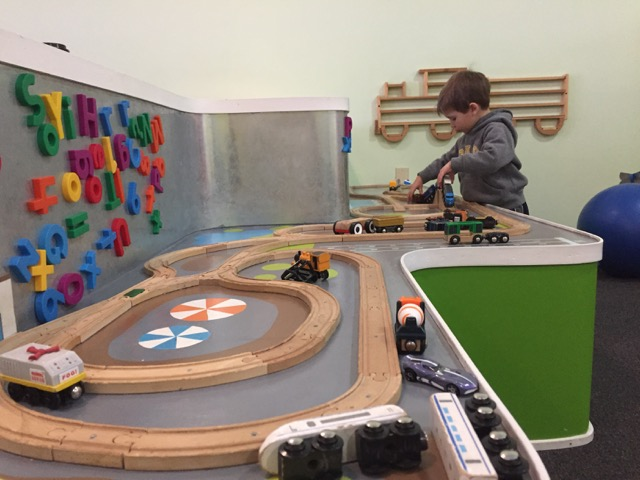 boy playing with train at peapod play cafe