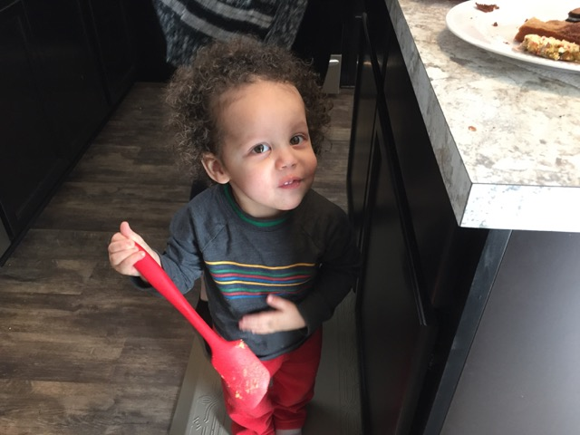 Little boy licking spatula