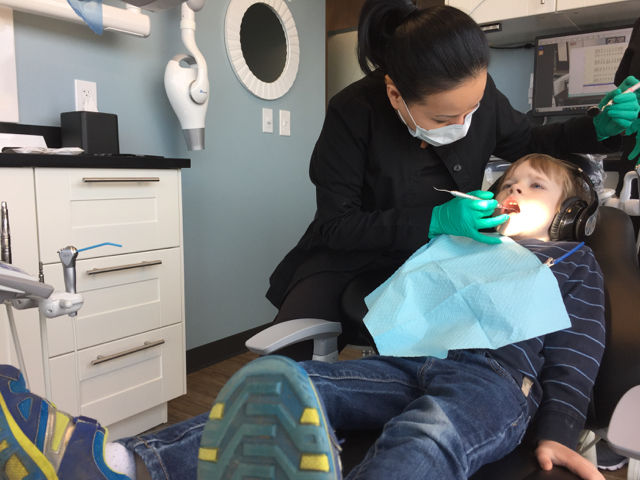 Dentist checking kid's teeth at River Park Dental