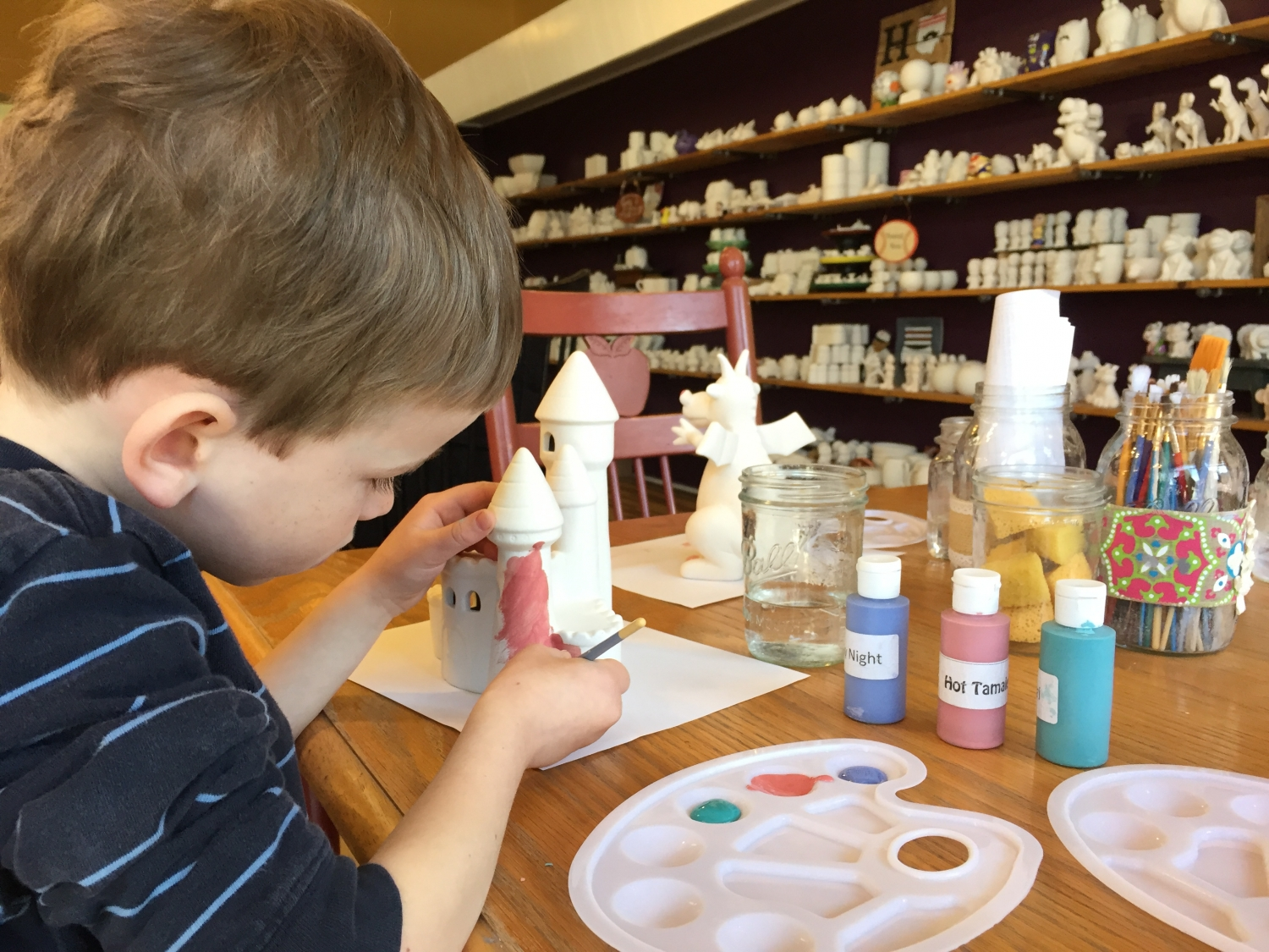 Boy painting pottery at The Studio in Hamilton, OH