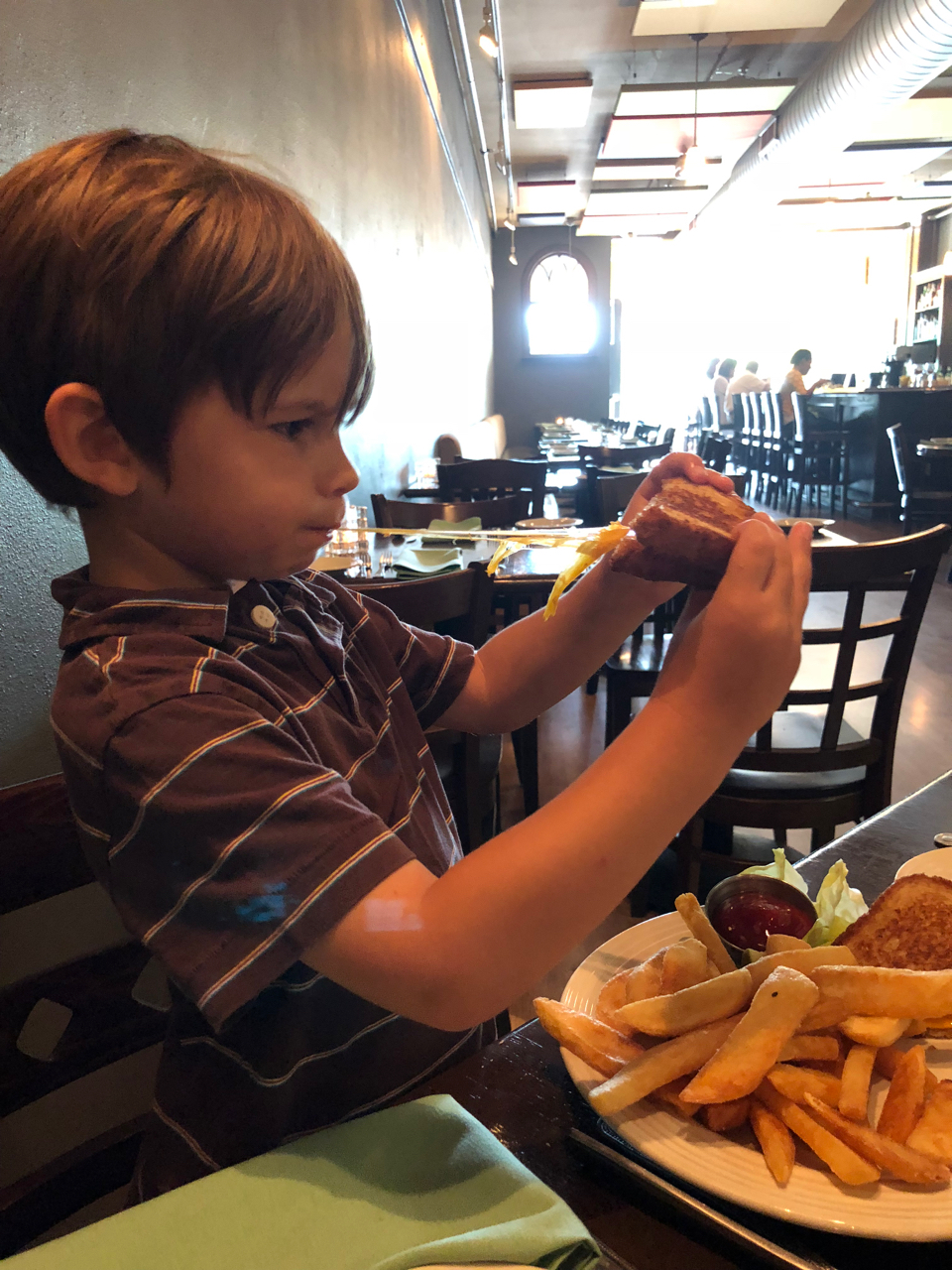 Boy eating grilled cheese at Seasons Bistro in Springfield, Ohio