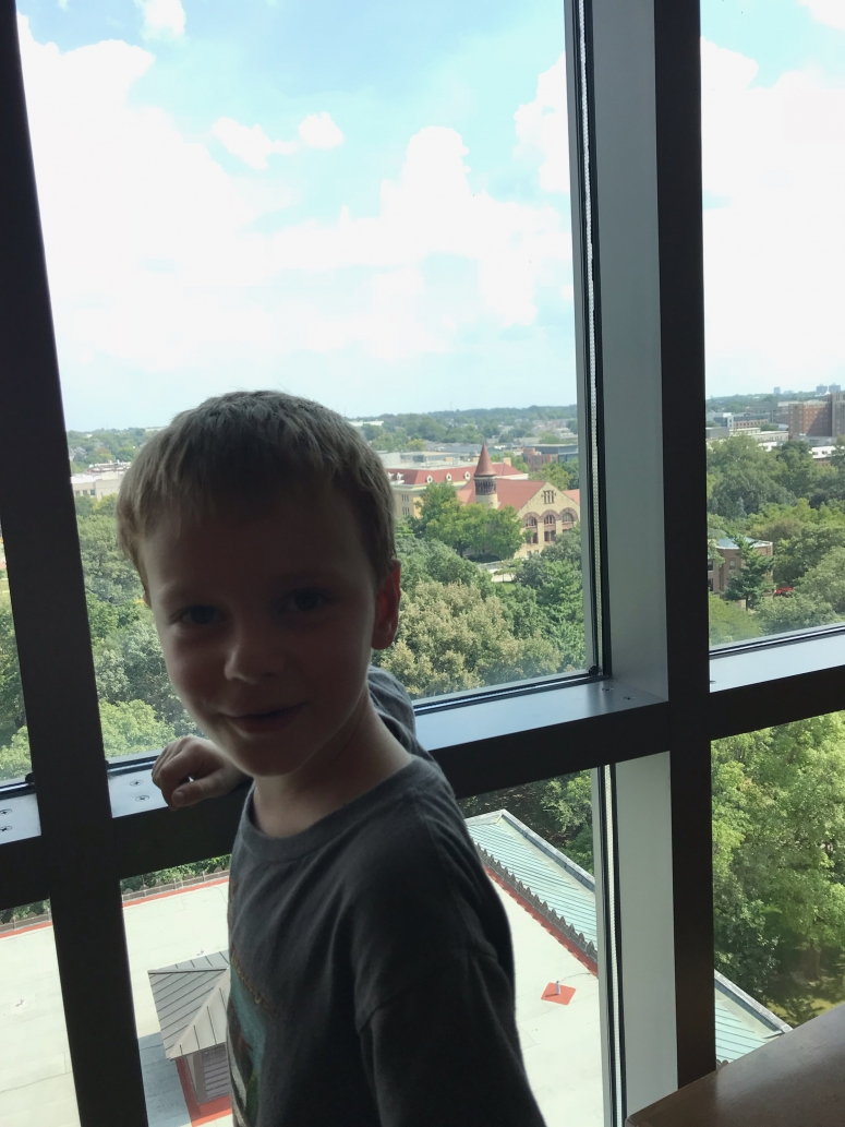 kid looking out the window at Thompson Library, Ohio State University Campus