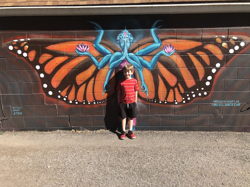 boy standing against mural in Yellow Springs, Ohio