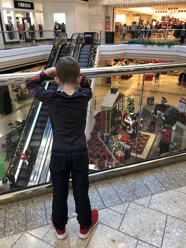 boy standing in Mall at Tuttle Crossing looking down on Santa.