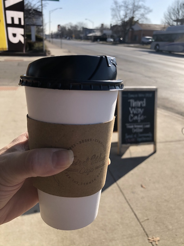 coffee cup held up outside Third Way Cafe