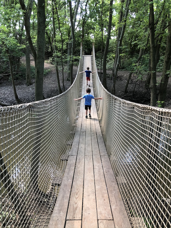 two boys walking the rope bridge in Scioto Grove Metro Park