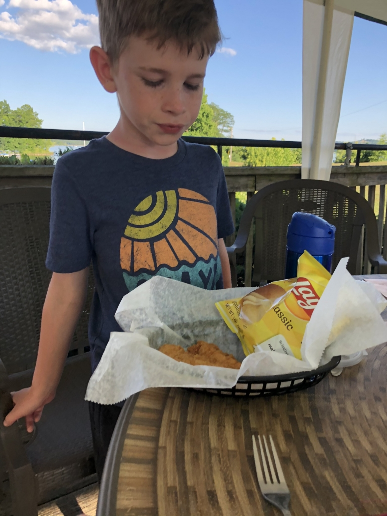 boy eating food at the Dockside Restaurant at Seneca Lake Marina