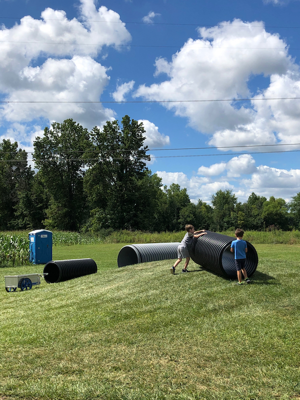 two boys pushing an empty tube up a hill to roll down at Hendren Farm Market