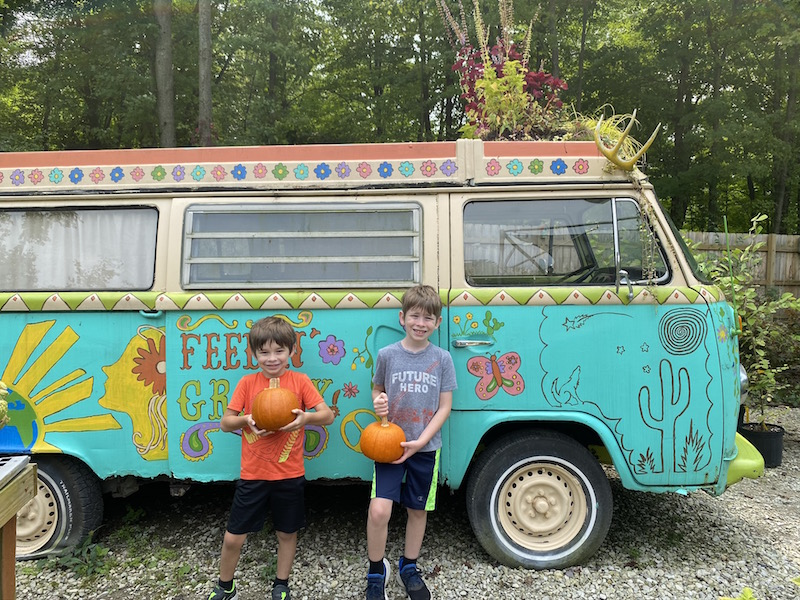 Two boys holding pumpkins in front of the VW Bus at Groovy Plants Ranch