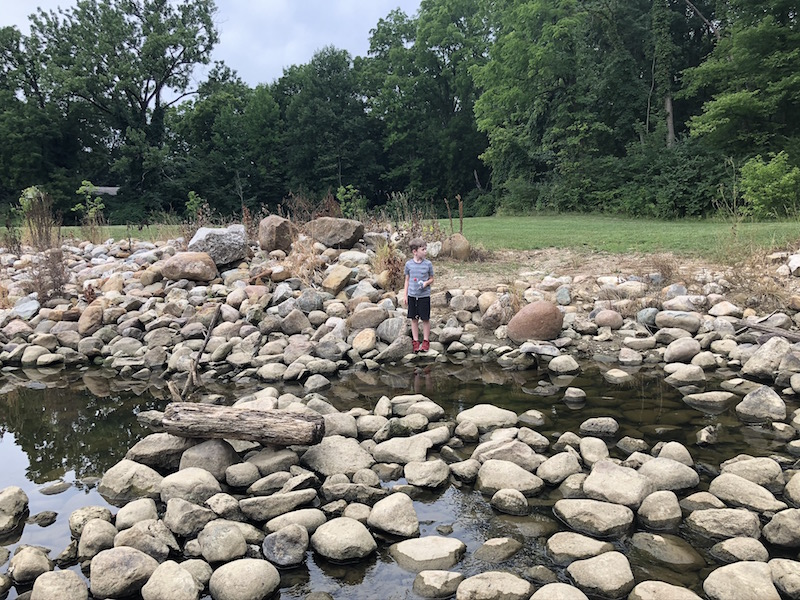 boy walking on the rocks in the creek