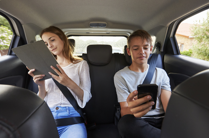 boy and girl looking at devices in the car