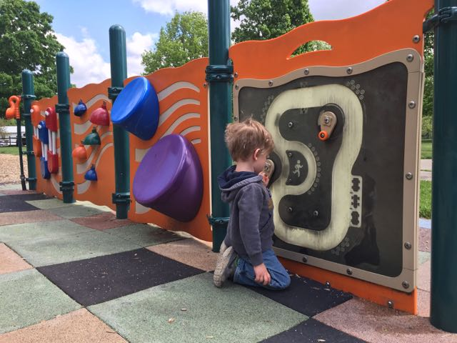 little boy playing on a wall of toddler activities at Friendship Park in Gahanna, Ohio.