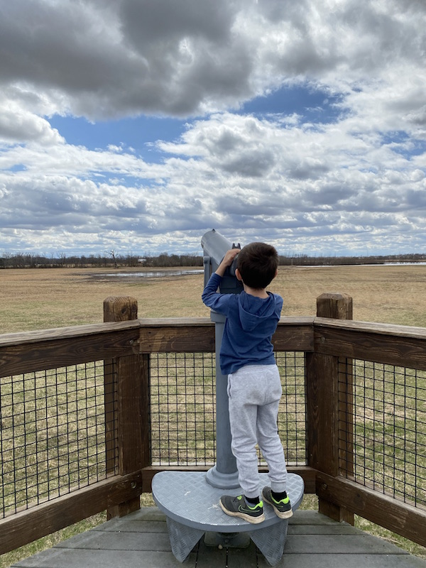 boy looking through binoculars at the observation deck at Glacier Knoll Picnic Area.