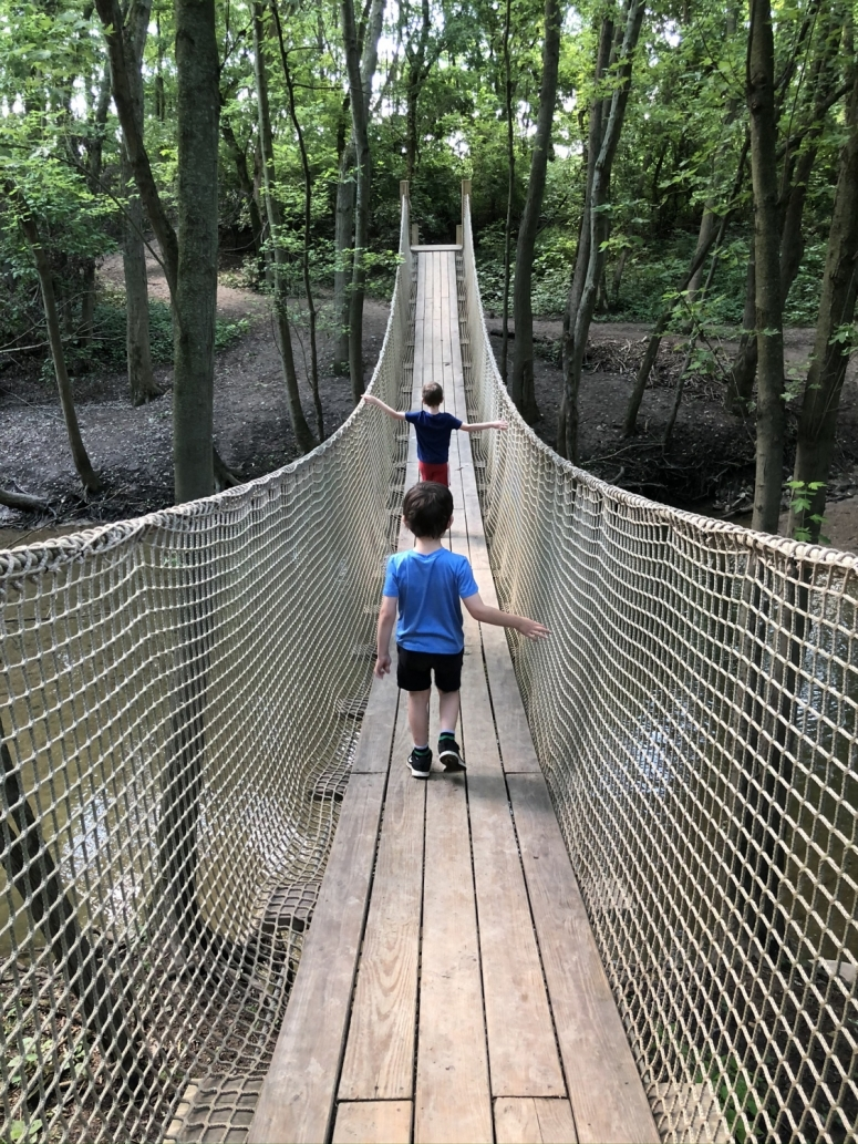 two boys walking across the rope bridge at Scioto Grove Metro Park in Grove City, Ohio.