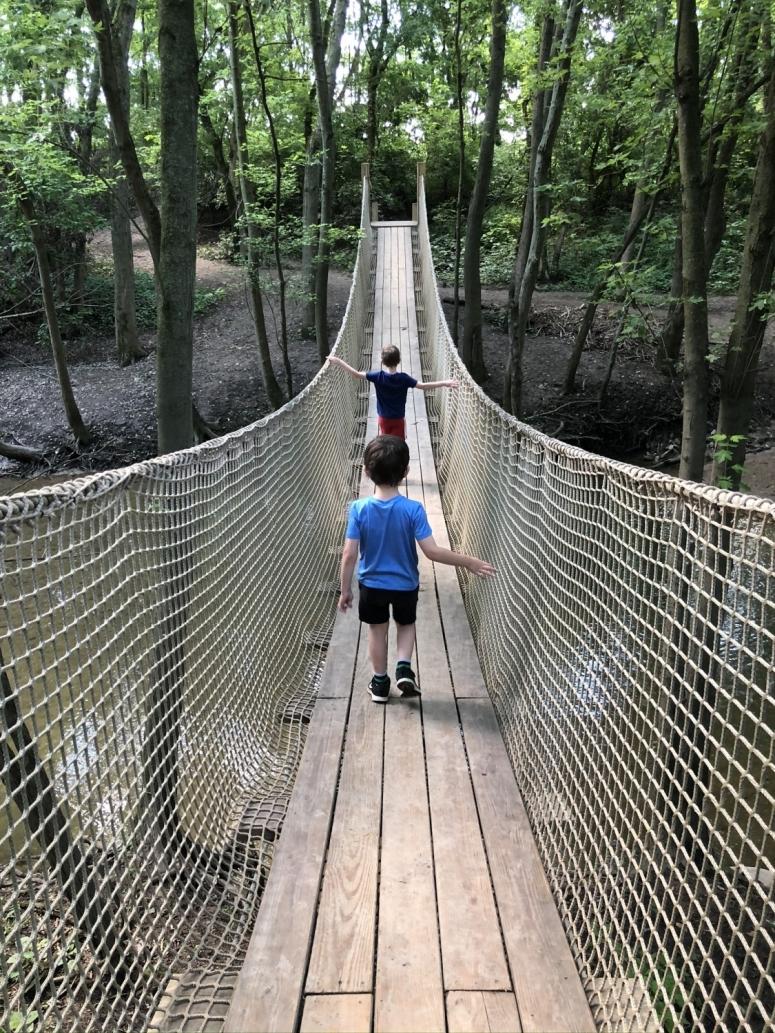 two boys walking across the rope bridge at Scioto Grove Metro Park in Grove City, Ohio.