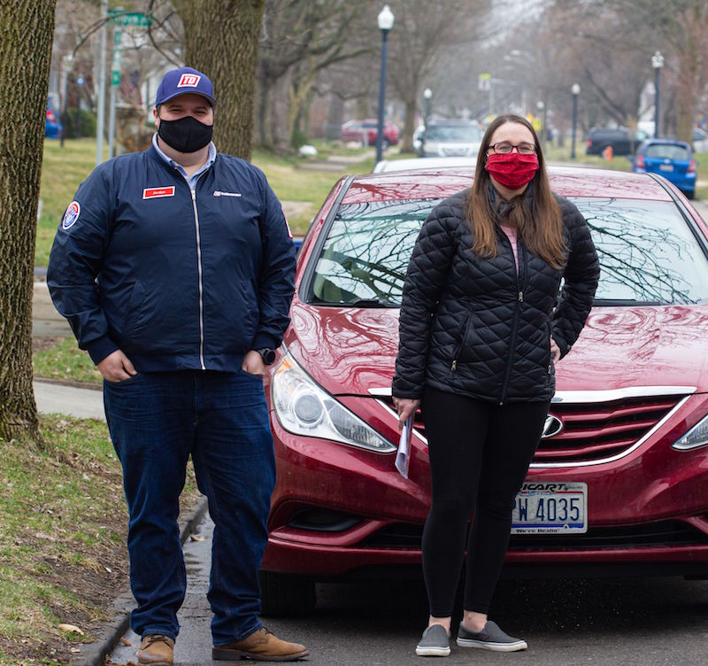 man and woman standing in front of a red car.