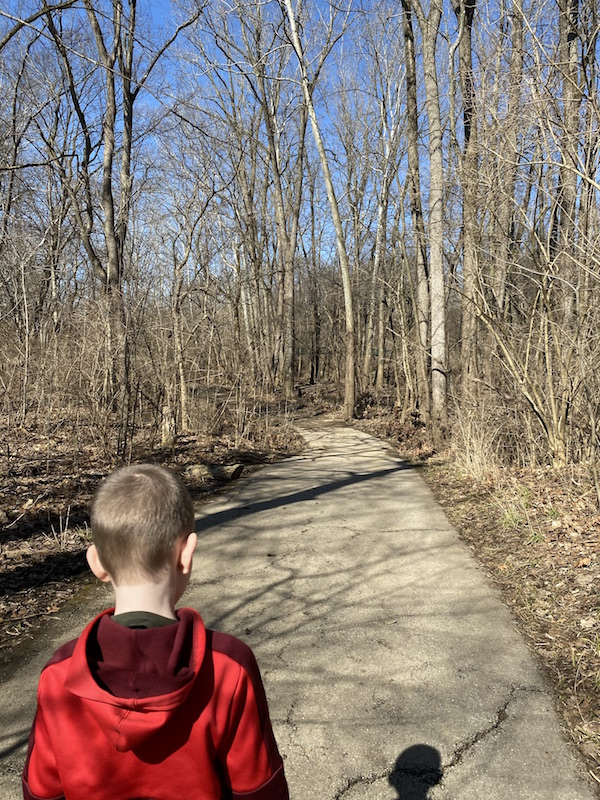 a boy walking on the multi-purpose trail in woodside green park in gahanna.