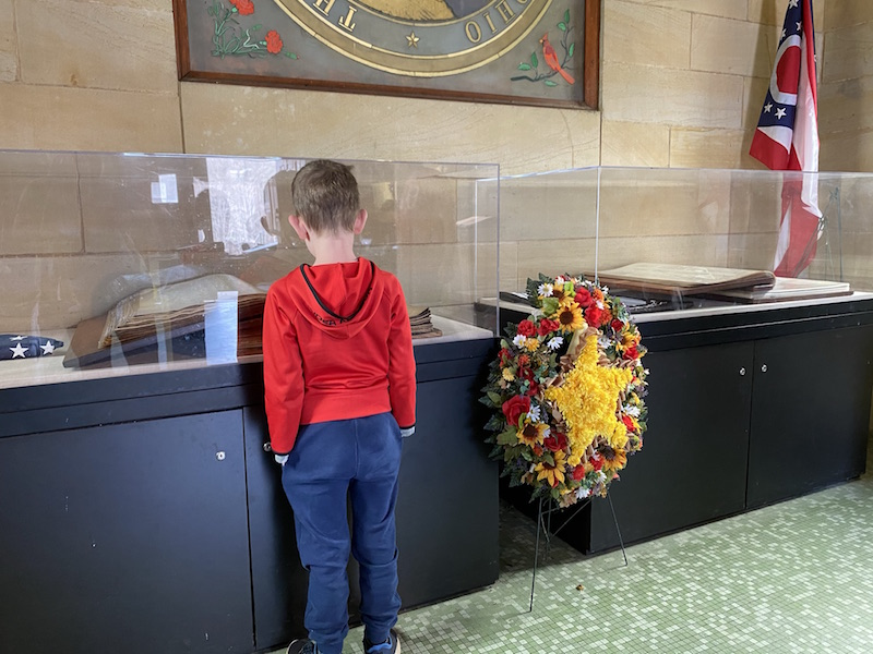 boy looking at the books under glass at the Ohio Memorial Forest Shrine.