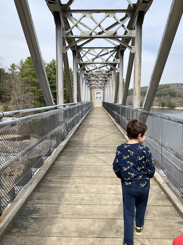 boy walking on the bridge at Pleasant Hill Dam in Mohican State Park.