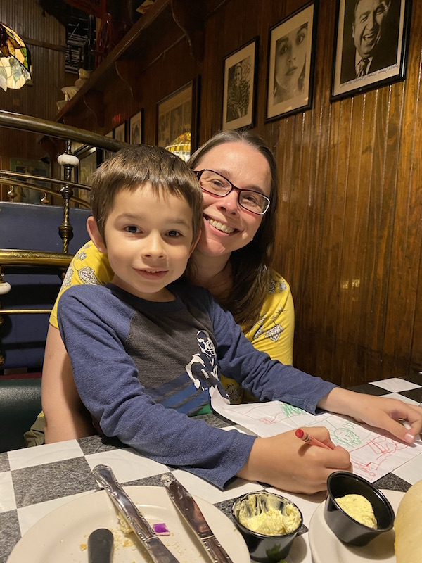 boy sitting on mom's lap in a restaurant booth.