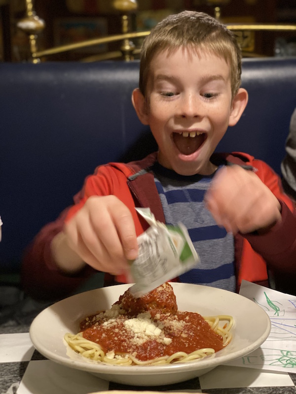 boy putting parmesan cheese on his spaghetti and meatballs.
