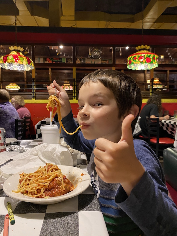boy eating spaghetti and giving a thumbs up.