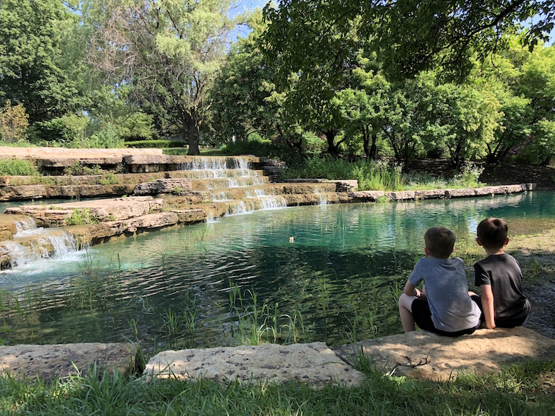 Two boys sitting in front of the Franklin Park Cascades.