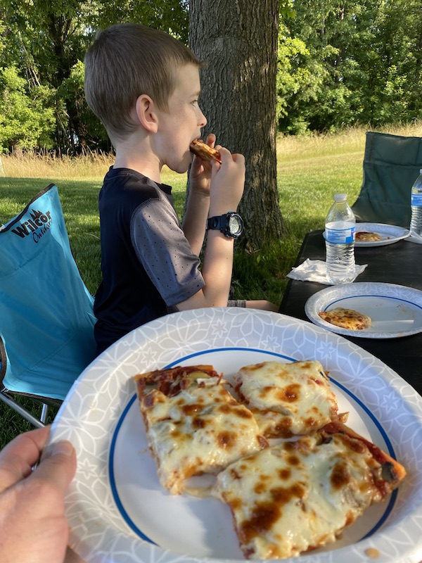 boy eating Phase Two Pizza in Perrysville Ohio.