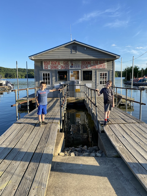 Two boys standing in front of Pleasant Hill Lake Marina.