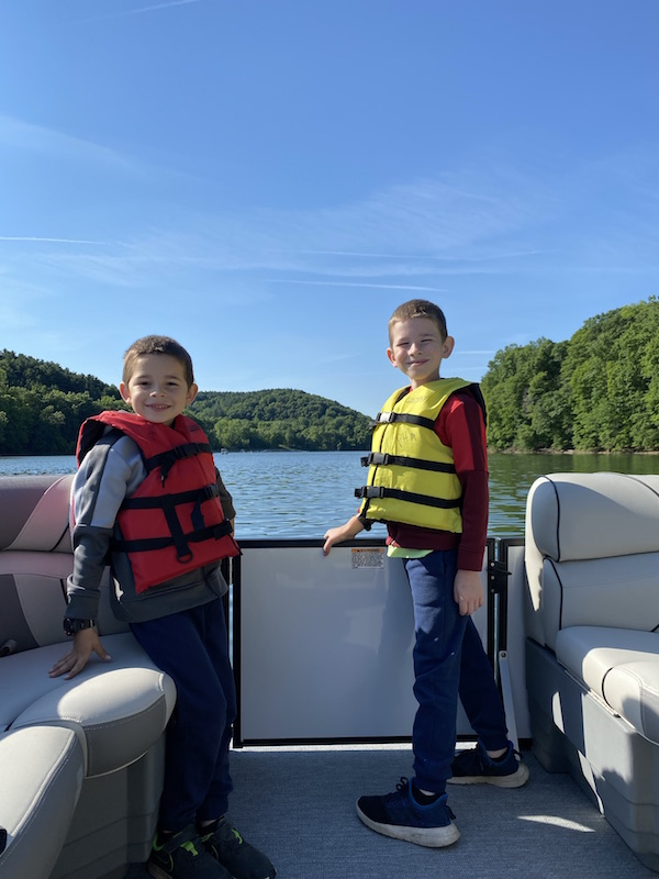 two boys on a pontoon boat at Pleasant Hill Lake.
