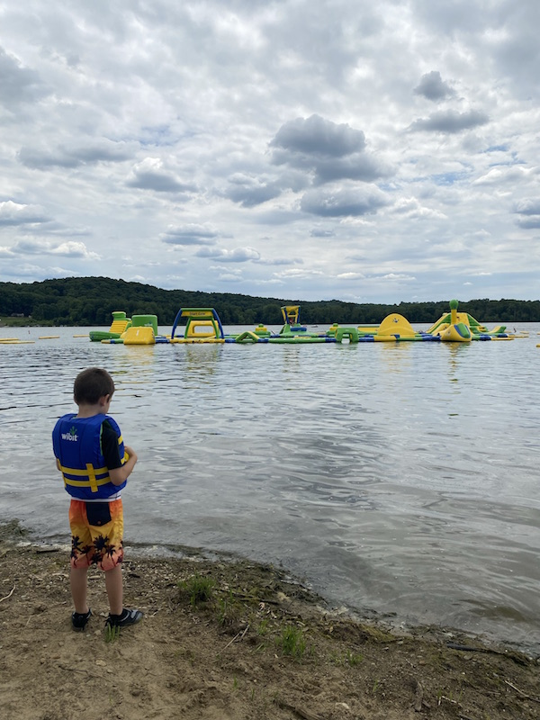 boy standing on the beach in front of the Whoa Zone at Pleasant Hill Lake.