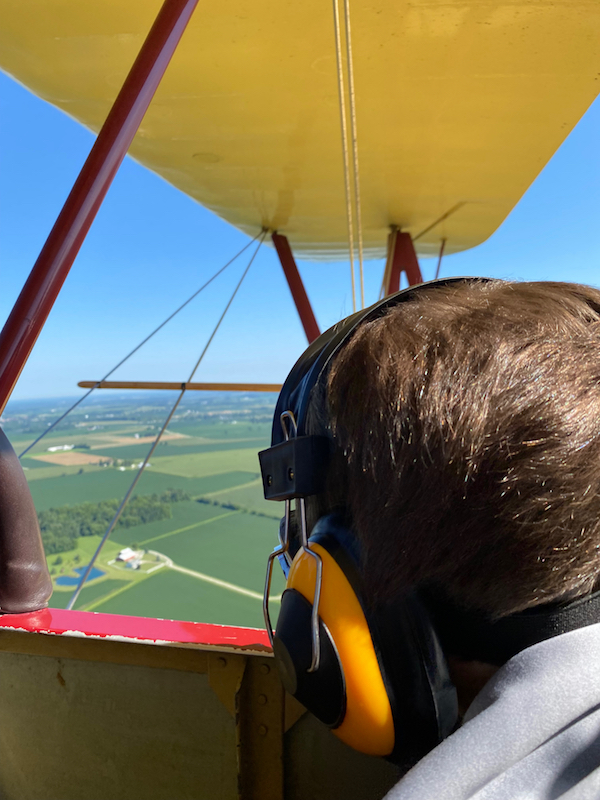 A boy looking at the view from a bi-plane flight at Goodfolk & O'Tymes Biplane Rides.