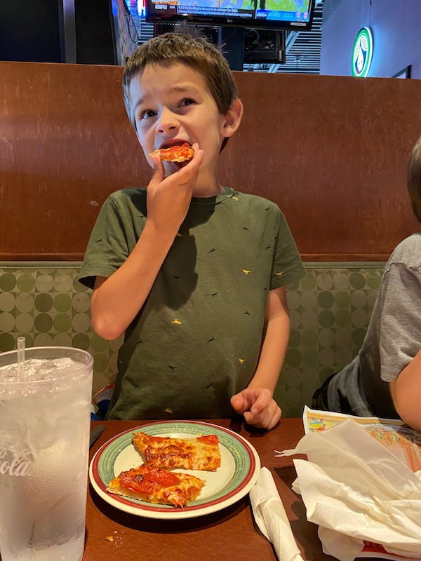 Boy eating pizza at Milano's in Greene County, Ohio.